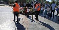 Сотрудники муниципального предприятия Тазалык убирают мусор с площади Победы