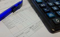 Төлөм квитанциясы, калькулятор жана калем столдо жатат. Архив