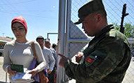 Пограничник КР проверяет паспорт на контрольно-пропускном пункте кыргызско-узбекской границы в Кара-Суу. Архивное фото