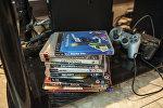 Стопка видеоигр и джойстик игровой консоли. Архивное фото