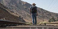 Архивное фото мужчины идущего вдоль железной дороги