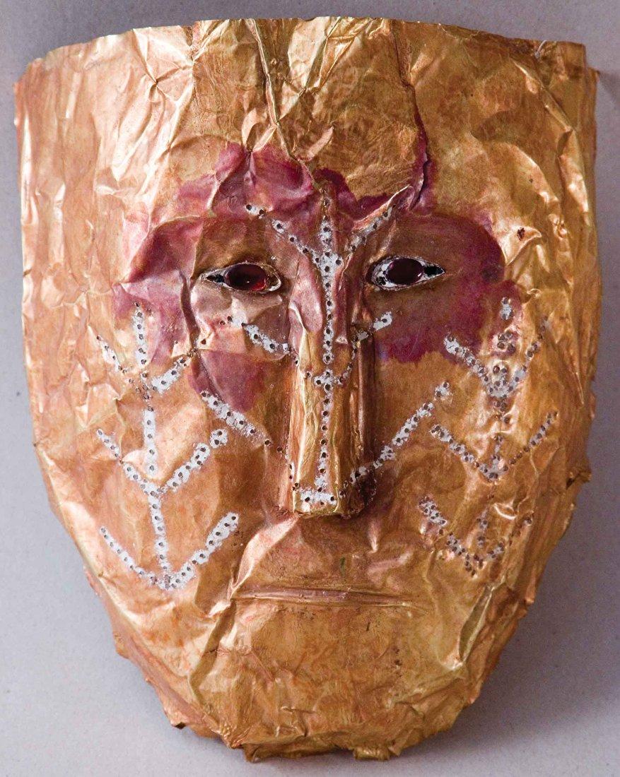 Маска лицевая из листового золота. Черты лица схематичны. Миндалевидные глаза с вставками из цветных камней. На щеки и нос маски нанесен рисунок в виде древа жизни, контуры заполнены белой пастой. Чуйская долина. Могильник Шамси IV–V веков нашей эры.
