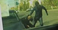 Кадр из видео, запечатлевшего, как молодой человек избивает пожилого водителя. Фото со страницы Instagram пользователя kazakh_video