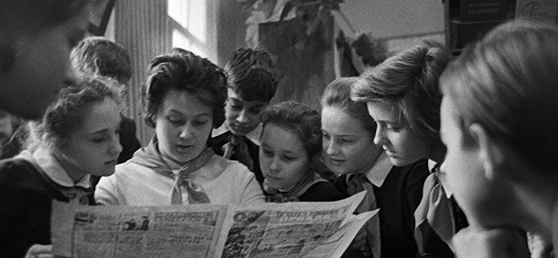 Вожатая читает ребятам газету Пионерская правда.