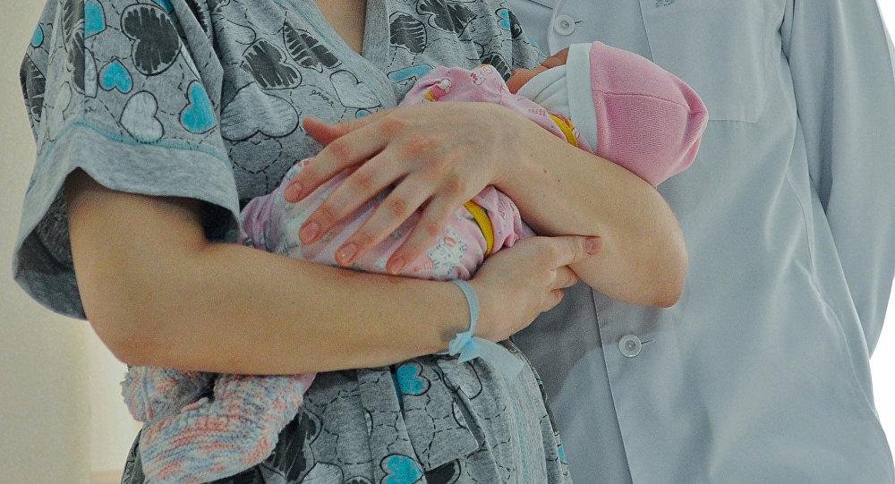 Женщина с новорожденным ребенком в руках. Архивное фото