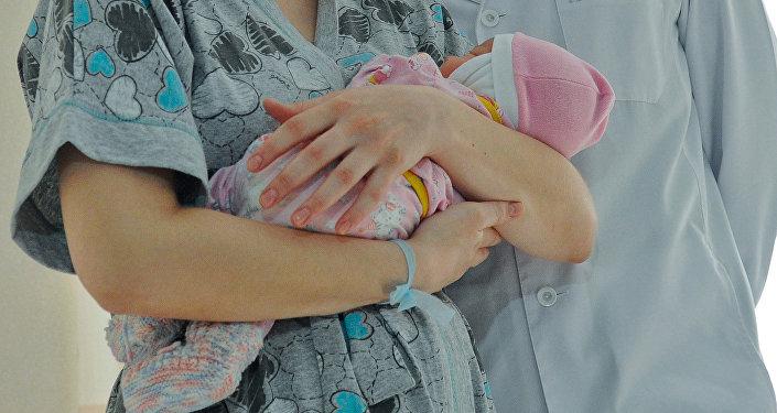 Женщина с новорожденным ребенком в руке. Архивное фото