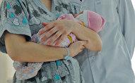 Девушка с грудным ребенком на руках. Архивное фото