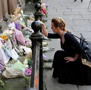 Женщина возлагает цветы жертвам нападения в Манчестер-Арене, в центре Манчестера. Архивное фото