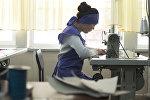 Сотрудница швейного цеха во время работы. Архивное фото