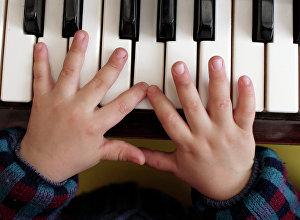 Рбеенок у фортепиано. Архивное фото