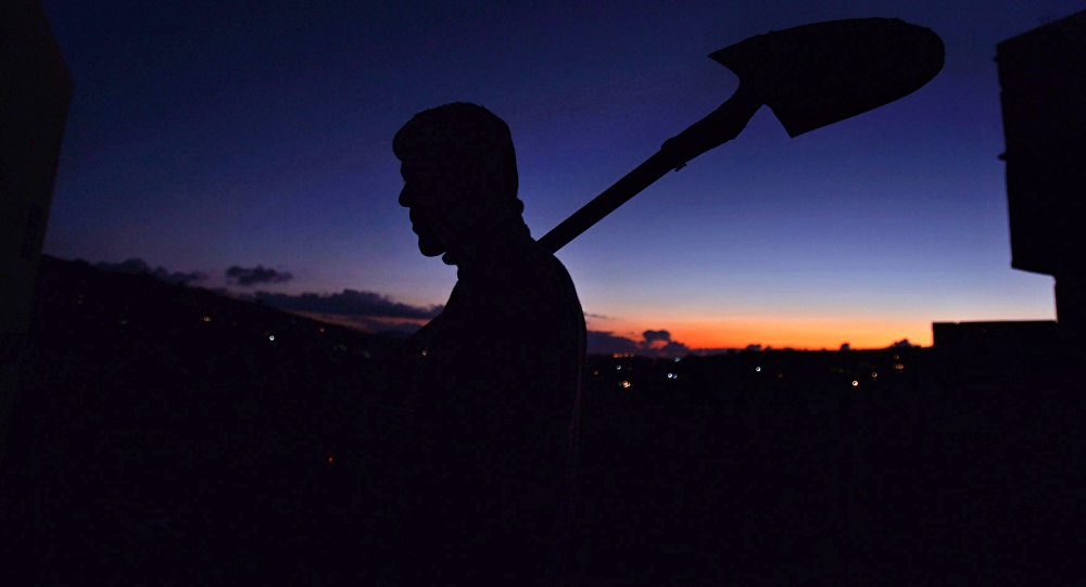 Мужчина держит лопату, на закате у своего дома. Архивное фото