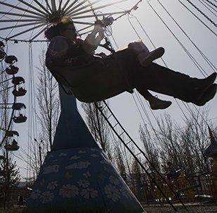 Женщина с ребенком на аттракционе на одном из парков Бишкека. Архивное фото