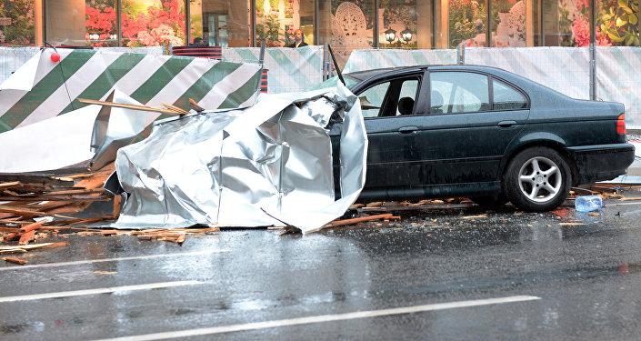 Сорванный ураганом рекламный щит на припаркованном автомобиле в Москве.
