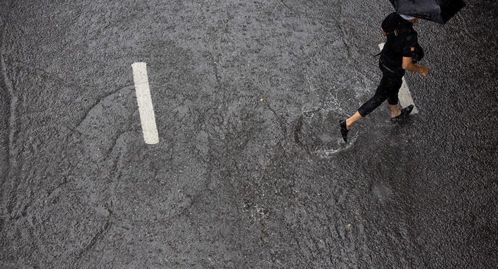 Женщина бежит во время ливня. Архивное фото
