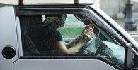 Водитель в машине во время дождя. Архивное фото