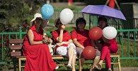 Женщины с воздушными шарами под зонтом отдыхают на скамейке в Бишкеке. Архивное фото