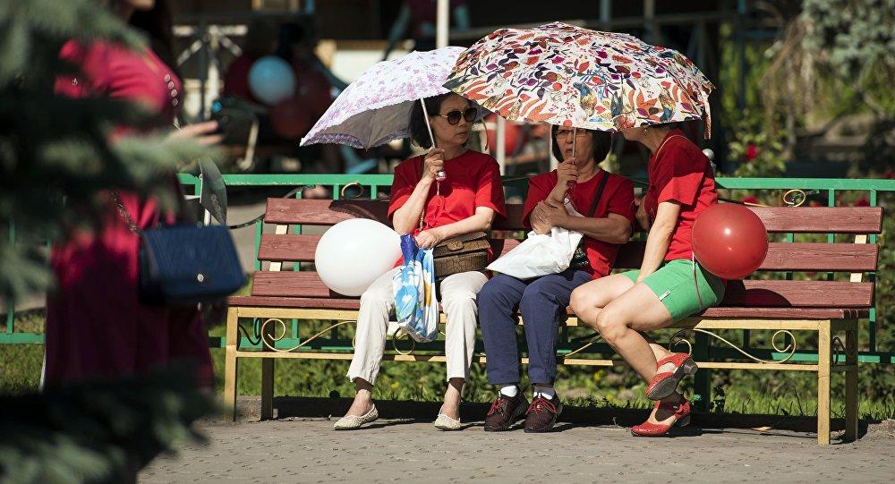 Женщины зонтом прикрываются от солнца. Архивное фото