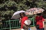 Женщины с зонтами на одной из улиц Бишкека. Архивное фото