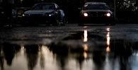 Отражение машин в луже после дождя. Архивное фото