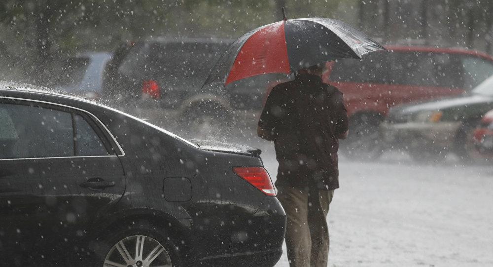 Мужчина с зонтом во время сильного дождя. Архивное фото