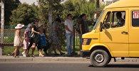 Горожане ждут общественный транспорт на остановке. Архивное фото