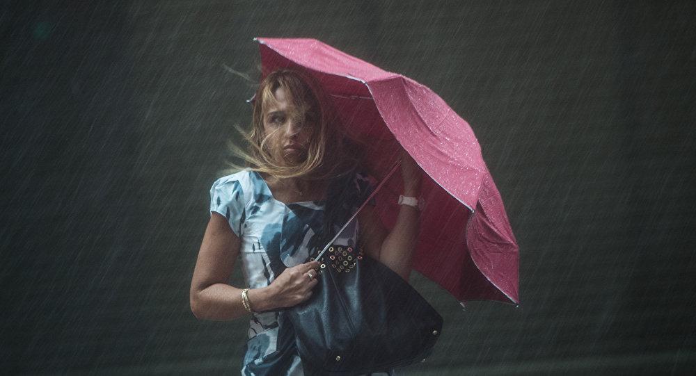 Женщина с зонтиком под сильным дождем и сильным ветром. Архивное фото