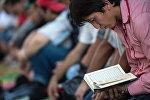 Намаз алдында куран китебин окуп жаткан адам. Архив