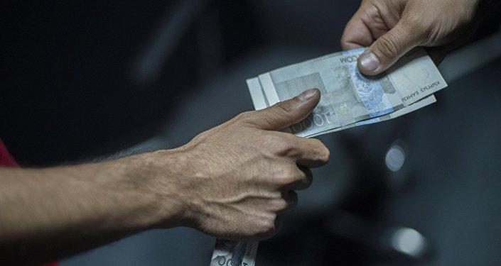 Мужчина передает деньги, некоторые купюра пряча в руке. Архивное фото