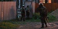 Сотрудники Росгвардии стоят в оцеплении на одной из улиц поселка Кратово, где мужчина забаррикадировался в своем доме и стал стрелять по людям из окна