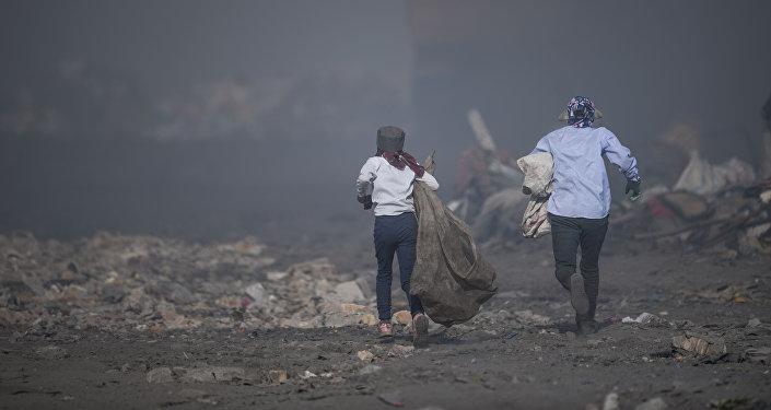 Женщина с ребенком на мусорном полигоне в Бишкеке