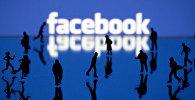 Силуэты людей на фоне логотипа социальной сети Facebook. Архивное фото