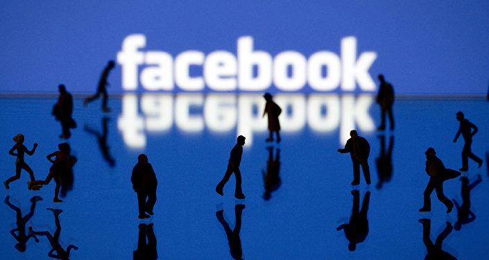 Силуэты людей на фоне логотипа социальной сети Facebook