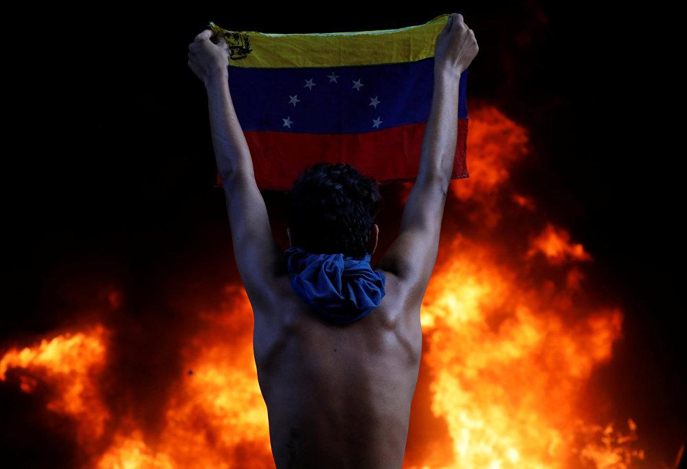 Каракаста Жогорку соттун имаратынын алдында нааразычылыкка чыккан жаран Венесуэланын улуттук желегин көтөрүп турат. Имарат президент Николас Мадурого каршы чыккан митингчилер тарабынан өрттөлгөн
