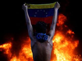 Протестующий держит национальный флаг Венесуэлы возле здания Верховного суда в Каракасе.