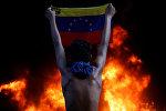 Каракаста Жогорку соттун имаратынын алдында нааразычылыкка чыккан жаран Венесуэланын улуттук желегин көтөрүп турат.