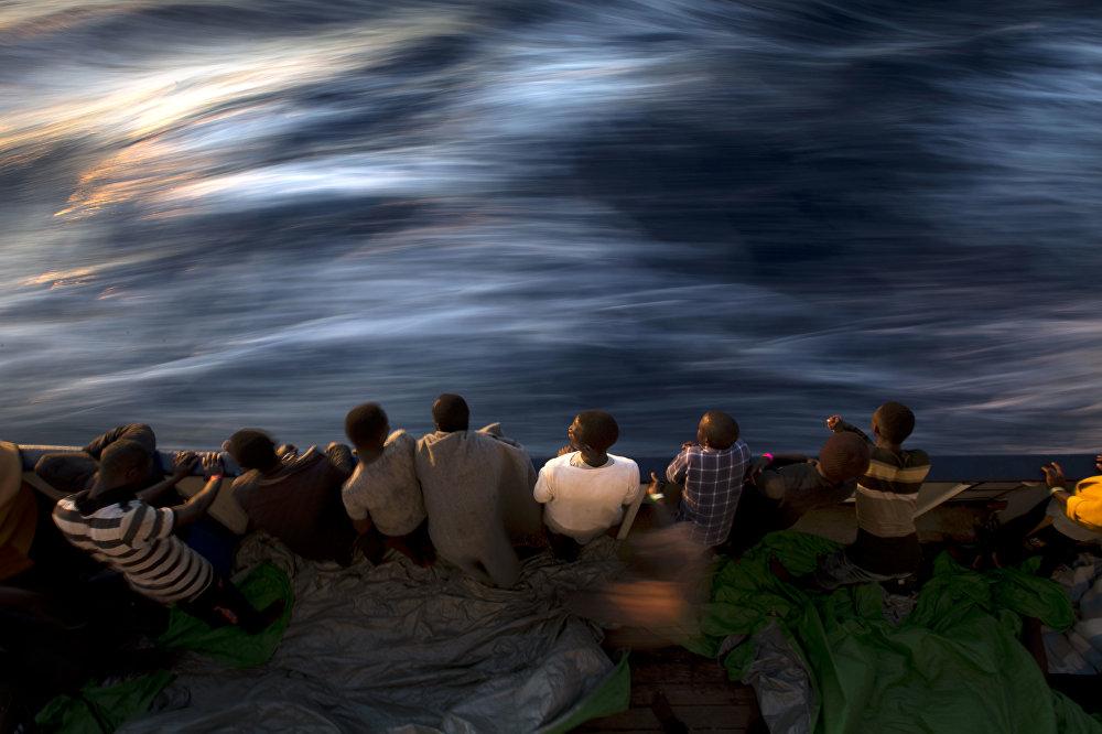 Мигранты и беженцы стоят на палубе спасательного судна
