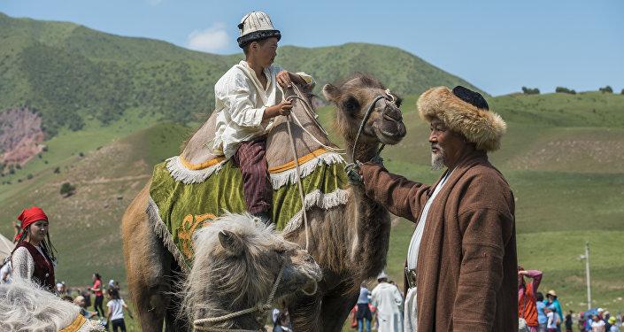 Мужчина в национальном костюме катает ребенка на верблюде. Архивное фото