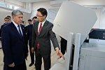 Президент КР Алмазбек Атамбаев и заместитель председателя Государственной регистрационной службы Дастан Догоев (справа) во время ознакомления в работой системы изготовления биометрических электронных паспортов
