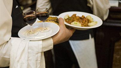 Официант разносит еду и вино посетителям ресторана. Архивное фото
