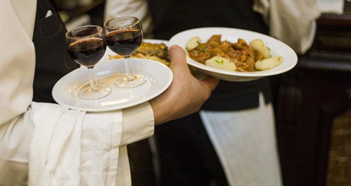 Официант разносит еду и вино посетителям кафе. Архивное фото