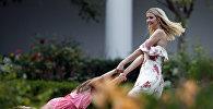 Дочь президента США Иванка Трамп играет со своей дочерью на лужайке Белого дома в Вашингтоне