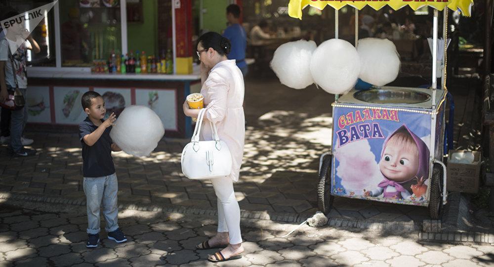 Женщина с ребенком у точки продажи сладкой ваты в парке Панфилова в Бишкеке. Архивное фото