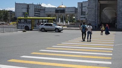 Пешеходы переходят дорогу на центральной площади Ала-Тоо в Бишкеке. Архивное фото