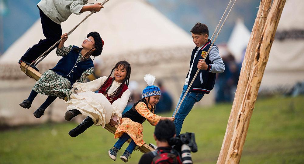 Дети качаются на качели. Архивное фото