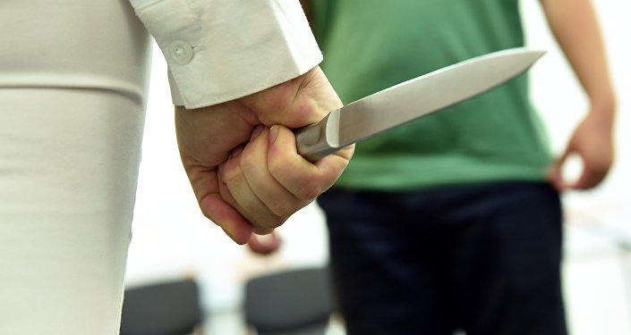 Девушка с ножом на фоне мужчины. Архивное фото