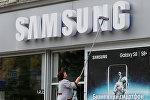 Сотрудница очищает корпоративный логотип Samsung Electronics Архивное фото