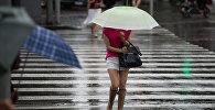 Женщина с зонтом идет по улице во время дождя. Архивное фото