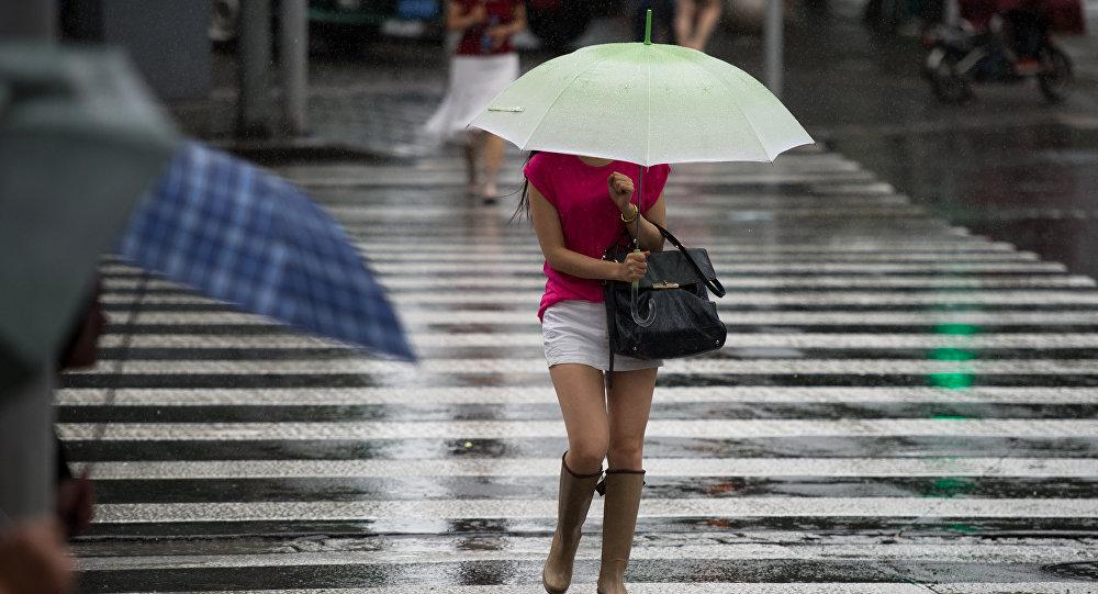 Женщина держит зонтик на улице города во время дождя. Архивное фото