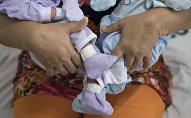 Женщина с новорожденными близнецами. Архивное фото