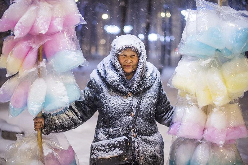 Продавщица сладкой ваты во время обильного снегопада в Бишкеке
